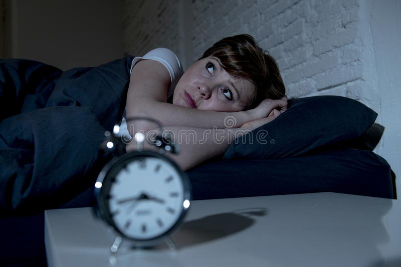 Mujer hermosa joven que miente en cama tarde en la noche que sufre del insomnio que intenta dormir imagen de archivo
