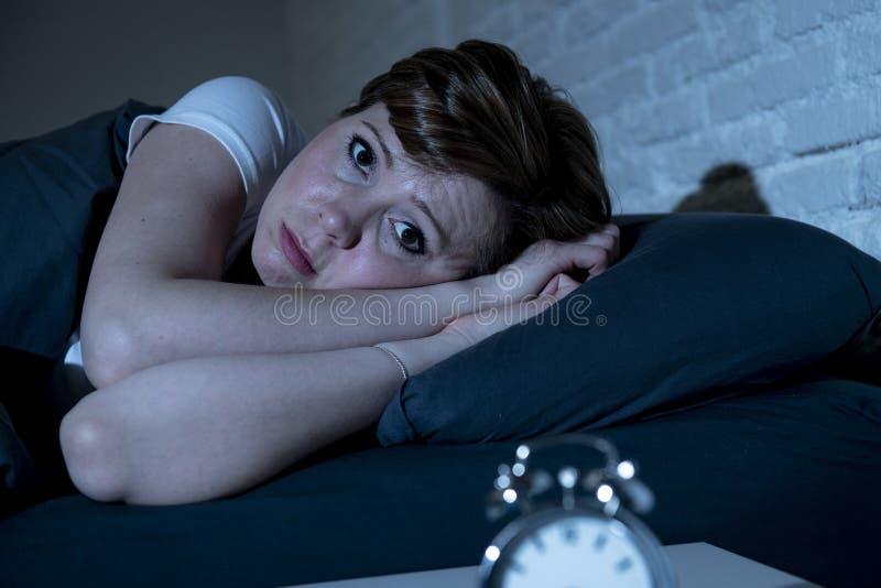 Mujer hermosa joven que miente en cama tarde en la noche que sufre del insomnio que intenta dormir imagen de archivo libre de regalías