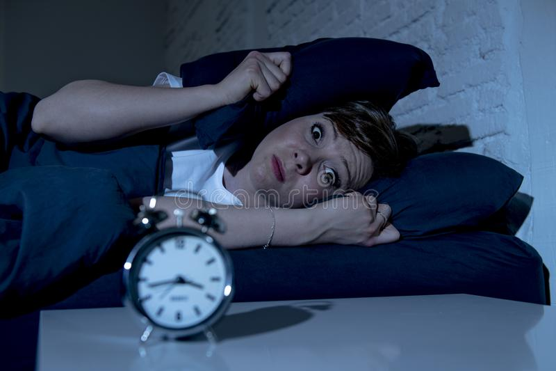 Mujer hermosa joven que miente en cama tarde en la noche que sufre del insomnio que intenta dormir imágenes de archivo libres de regalías
