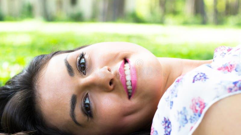 Mujer hermosa joven que miente en hierba imagen de archivo