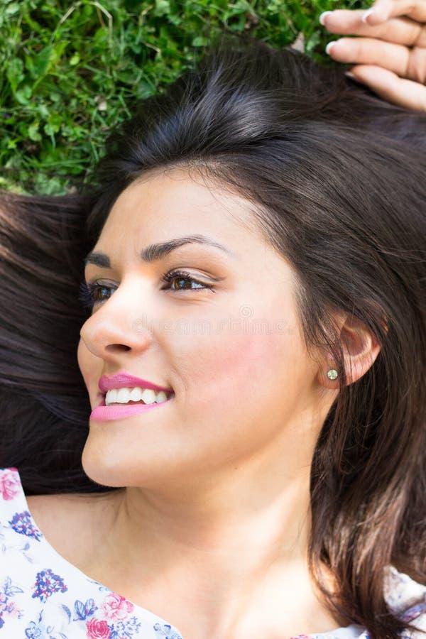 Mujer hermosa joven que miente en hierba foto de archivo libre de regalías