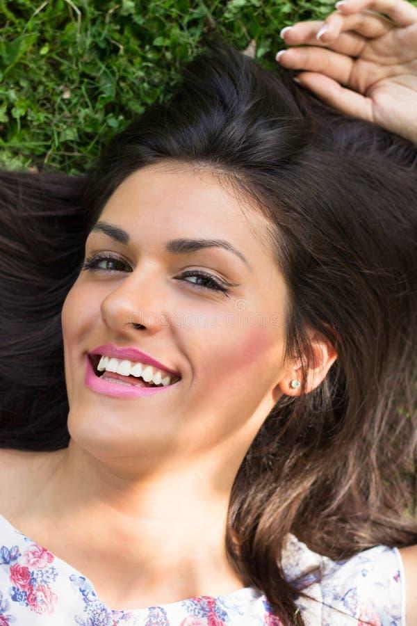Mujer hermosa joven que miente en hierba foto de archivo