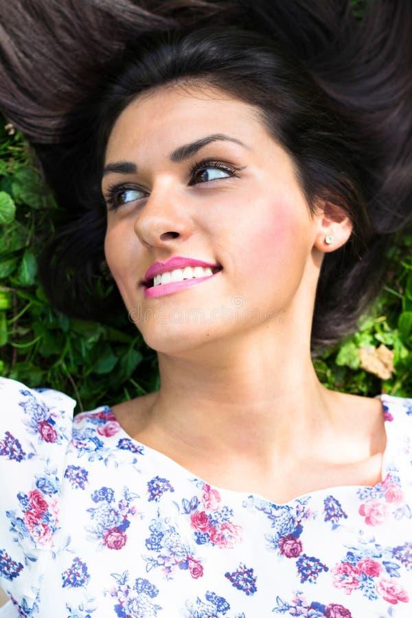 Mujer hermosa joven que miente en hierba fotografía de archivo
