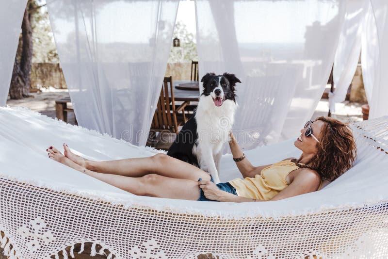 Mujer hermosa joven que miente en la hamaca con su perro del border collie al aire libre Forma de vida de la diversión y del vera fotos de archivo libres de regalías