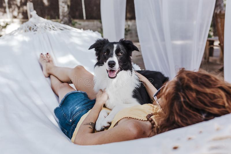 Mujer hermosa joven que miente en la hamaca con su perro del border collie al aire libre Forma de vida de la diversión y del vera imagen de archivo libre de regalías