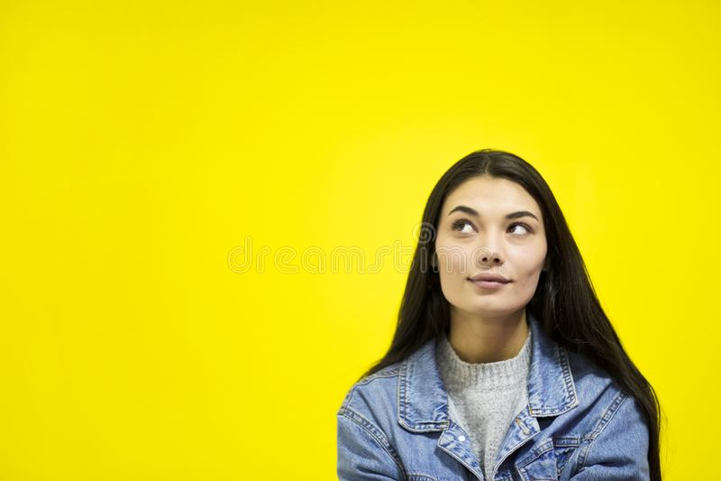 Mujer hermosa joven que mira lejos el espacio de la copia aislado en fondo amarillo fotografía de archivo libre de regalías