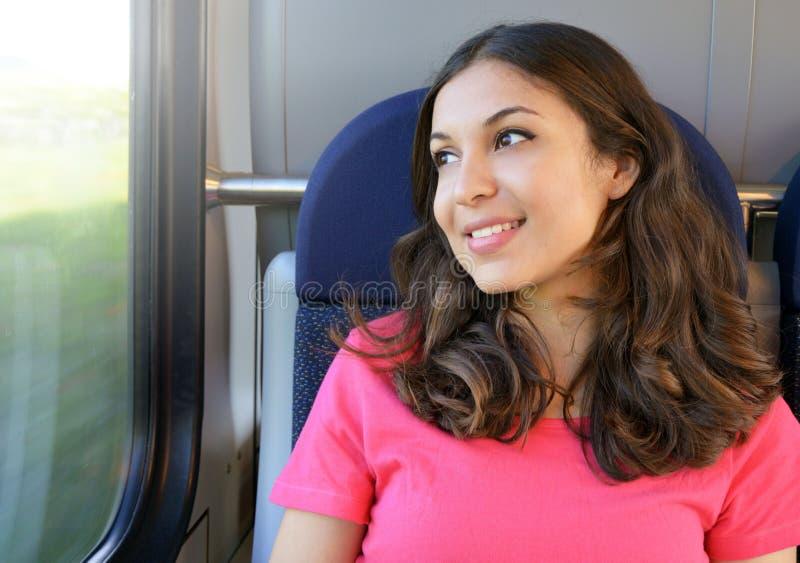 Mujer hermosa joven que mira a través de la ventana del tren El sentarse que viaja del pasajero feliz del tren en un asiento foto de archivo libre de regalías