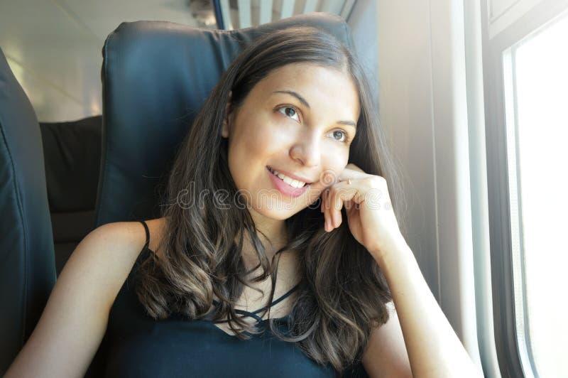Mujer hermosa joven que mira a través de la ventana del tren El sentarse que viaja del pasajero feliz del tren en un asiento y mi fotos de archivo