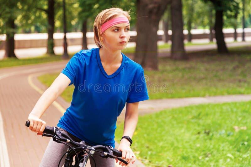 Mujer hermosa joven que monta una bicicleta en parque Gente activa outdoors imagen de archivo