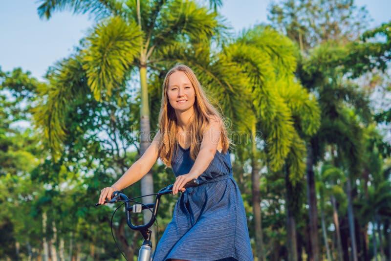 Mujer hermosa joven que monta una bicicleta en un parque Gente activa outdoor foto de archivo libre de regalías