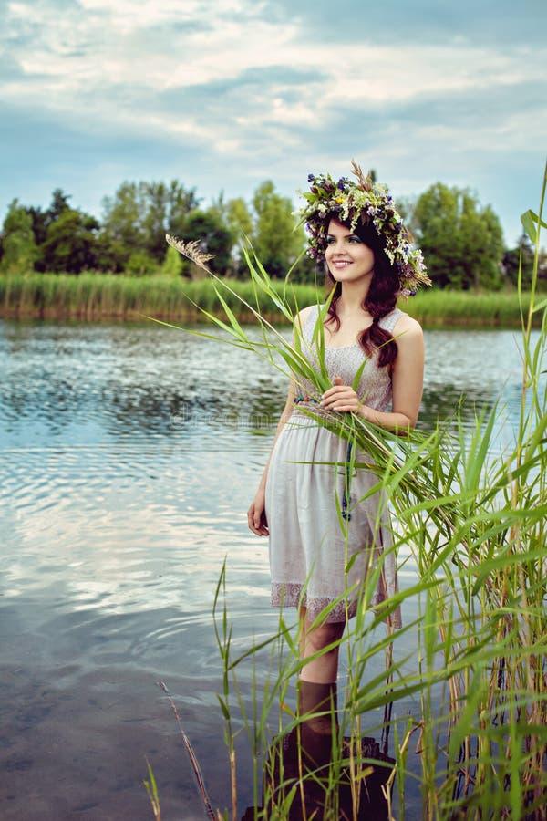 Mujer hermosa joven que permanece en el agua fotografía de archivo libre de regalías