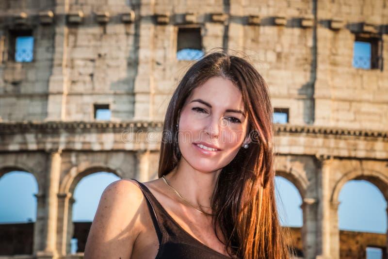 Mujer hermosa joven que presenta delante del Colosseum Ruinas de mármol de los arcos sobre un cielo azul, Roma, Italia fotos de archivo libres de regalías