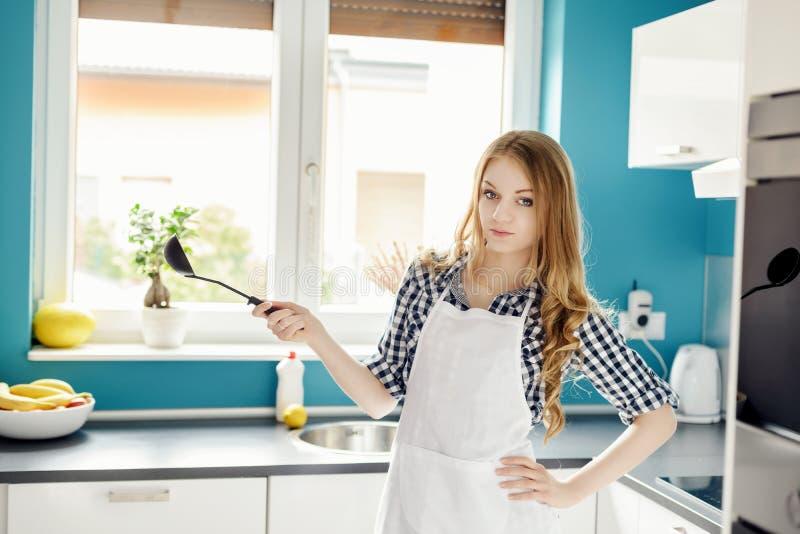 Mujer hermosa joven que presenta en la cocina con una cucharón imagen de archivo