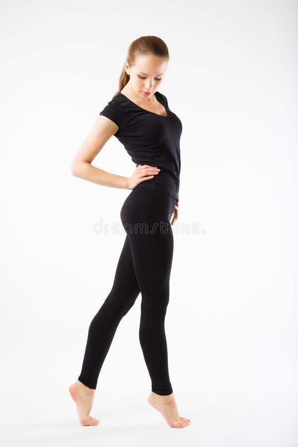 Mujer hermosa joven que presenta en un equipo del gimnasio muchacha sana joven con una figura perfecta imagen de archivo libre de regalías