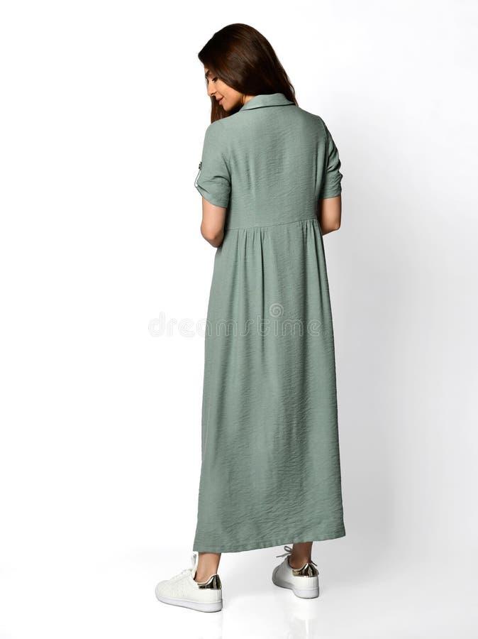 Mujer hermosa joven que presenta en vista posterior lateral trasera del nuevo vestido verde azul claro casual imagenes de archivo