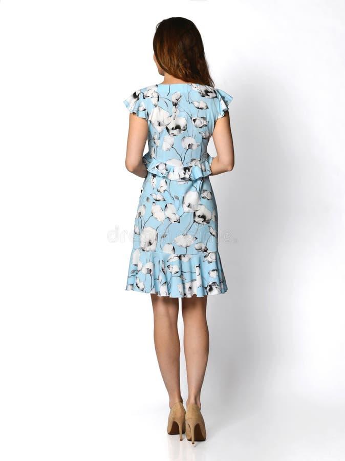 Mujer hermosa joven que presenta en vista posterior lateral trasera del nuevo vestido verde azul claro casual foto de archivo libre de regalías
