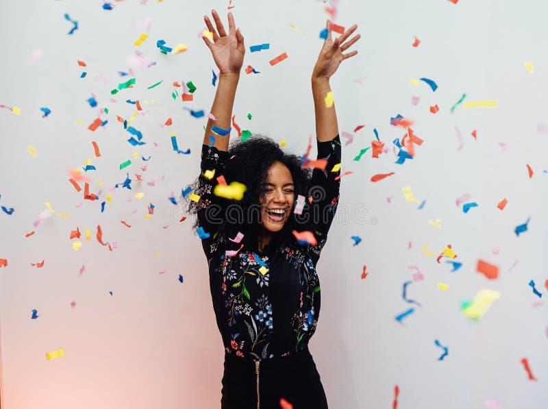 Mujer hermosa joven que ríe debajo de confeti colorido fotografía de archivo libre de regalías