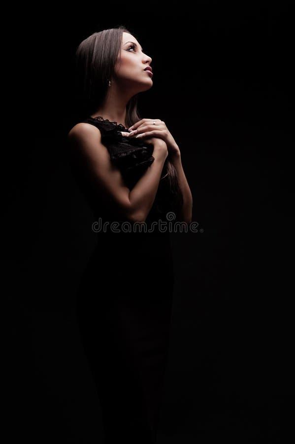Mujer hermosa joven que ruega en oscuridad imagenes de archivo