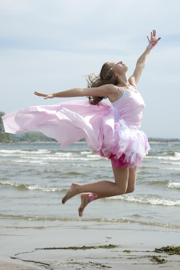 Mujer hermosa joven que salta en la playa. foto de archivo libre de regalías