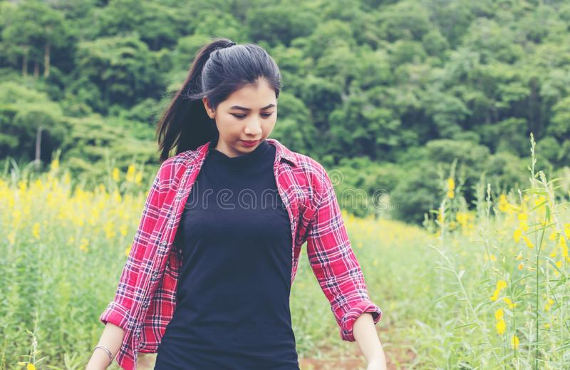 Mujer hermosa joven que se coloca en el disfrute del campo de flor fotografía de archivo libre de regalías