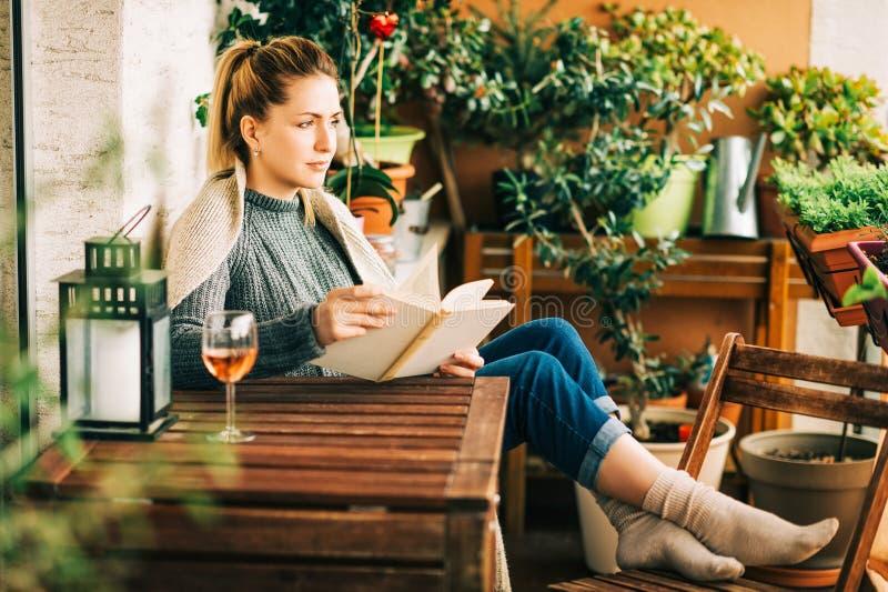 Mujer hermosa joven que se relaja en el balcón acogedor, leyendo un libro fotos de archivo