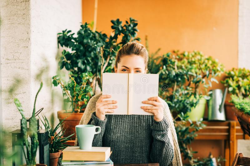 Mujer hermosa joven que se relaja en el balcón acogedor, leyendo un libro fotografía de archivo libre de regalías