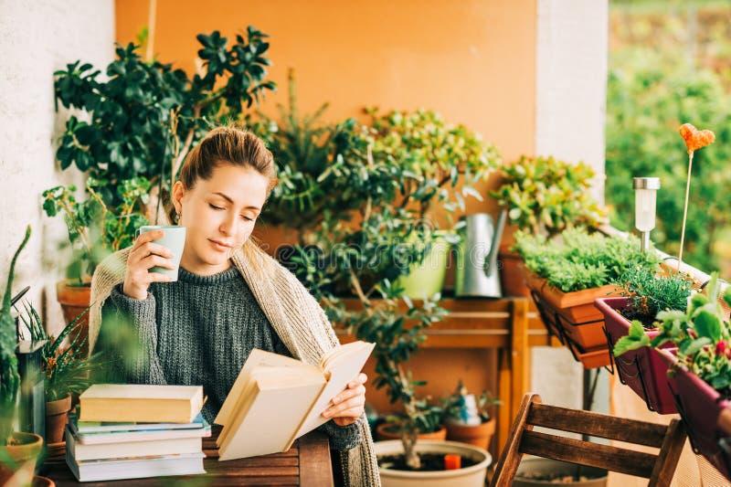 Mujer hermosa joven que se relaja en el balcón acogedor, leyendo un libro imagen de archivo libre de regalías