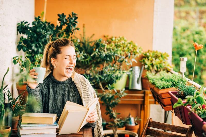 Mujer hermosa joven que se relaja en el balcón acogedor, leyendo un libro foto de archivo libre de regalías