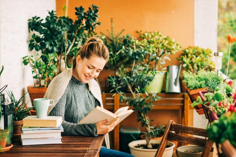 Mujer hermosa joven que se relaja en el balcón acogedor, leyendo un libro fotos de archivo libres de regalías