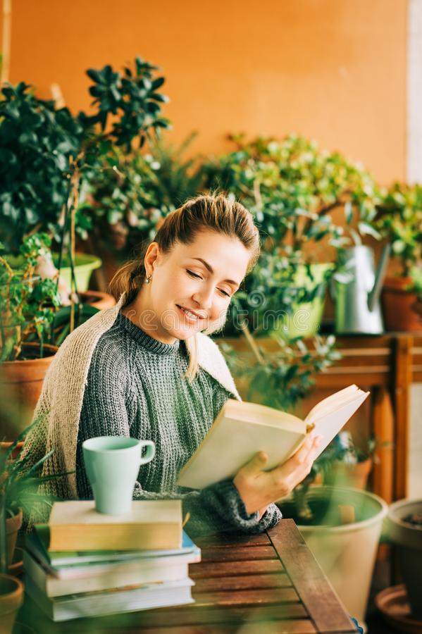 Mujer hermosa joven que se relaja en el balcón acogedor, leyendo un libro imagen de archivo