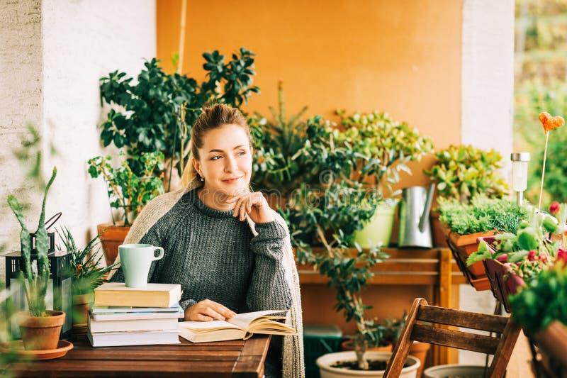 Mujer hermosa joven que se relaja en el balcón acogedor, leyendo un libro fotografía de archivo