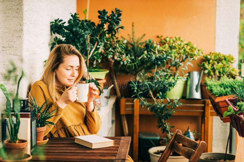 Mujer hermosa joven que se relaja en el balcón acogedor, leyendo un libro imagenes de archivo