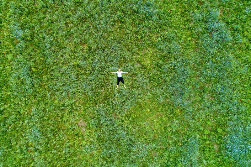 Mujer hermosa joven que se relaja en el campo con las flores Visi?n de arriba imagenes de archivo