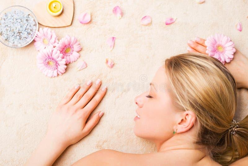 Mujer hermosa joven que se relaja en la tabla del masaje fotos de archivo libres de regalías
