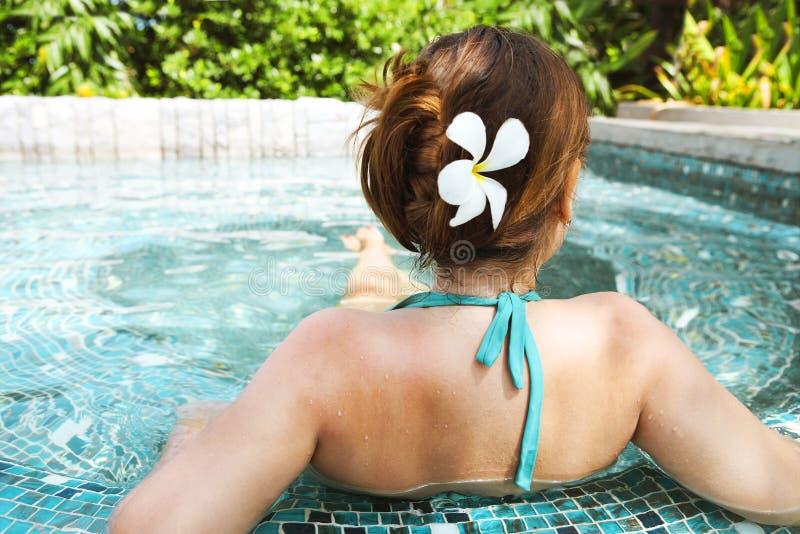 Mujer hermosa joven que se relaja en piscina del balneario foto de archivo
