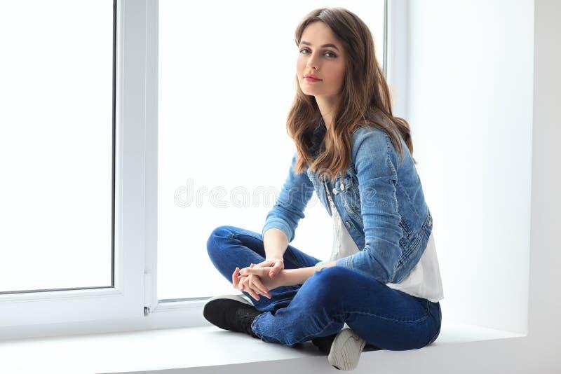 Mujer hermosa joven que se relaja en travesaño de la ventana imagen de archivo libre de regalías