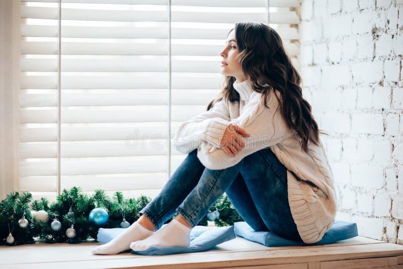 Mujer hermosa joven que se relaja en travesaño de la ventana en la decoración de la Navidad fotos de archivo libres de regalías