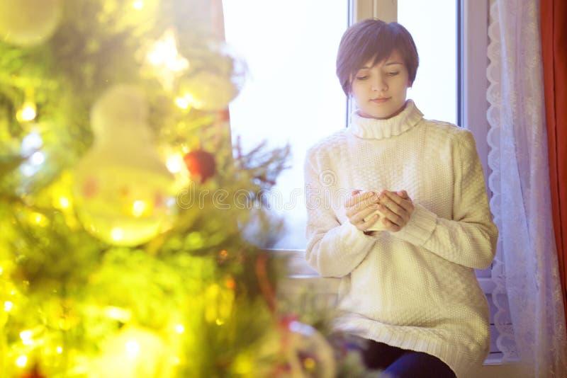 Mujer hermosa joven que se sienta a casa por la ventana con la taza de café caliente que lleva el suéter caliente hecho punto Árb imagen de archivo