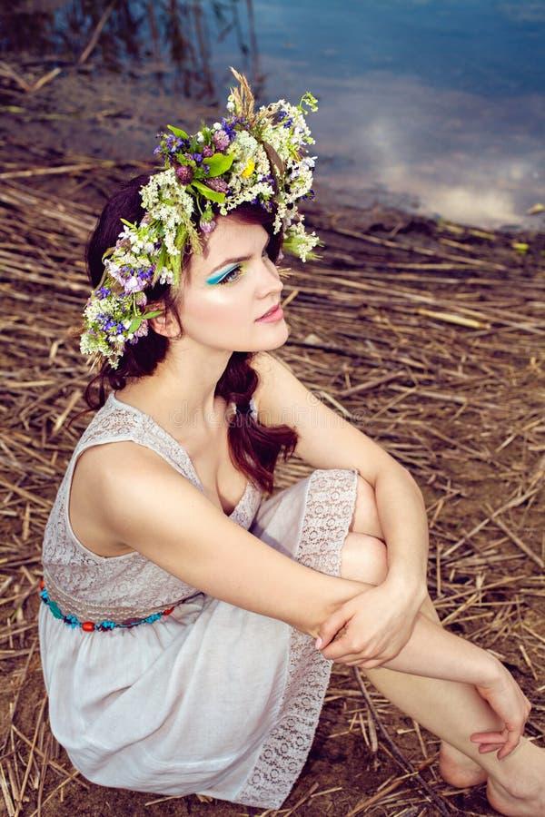 Mujer hermosa joven que se sienta cerca del agua del lago imagenes de archivo