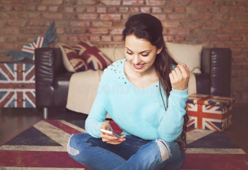 Mujer hermosa joven que se sienta con el teléfono elegante imágenes de archivo libres de regalías