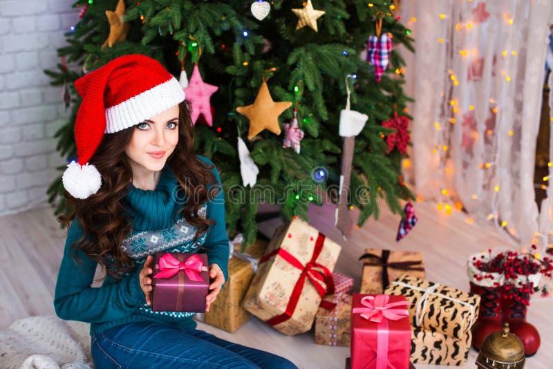 Mujer hermosa joven que se sienta debajo del árbol de navidad con el ` interior s del Año Nuevo fotos de archivo libres de regalías