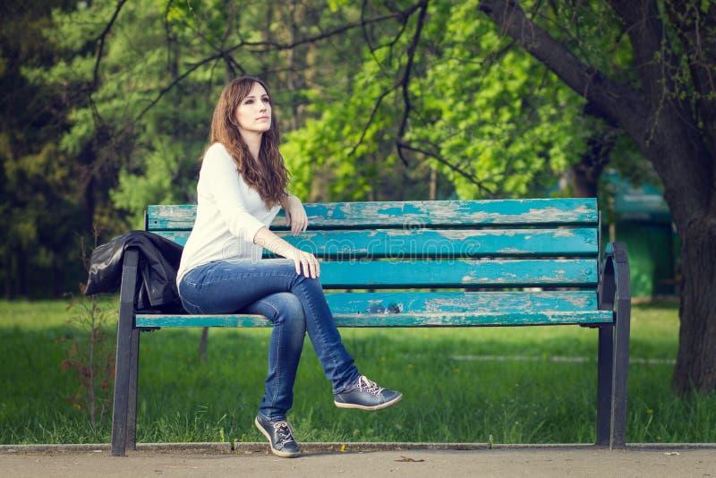 Mujer hermosa joven que se sienta en banco en parque imagenes de archivo
