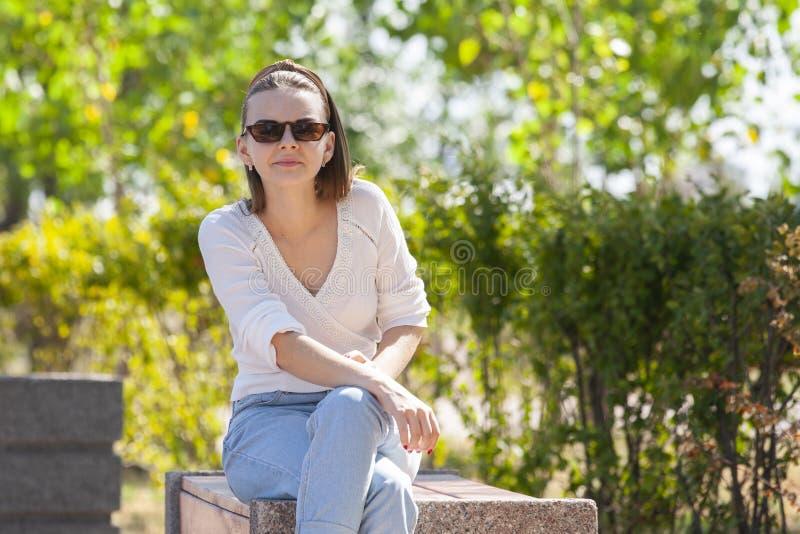Mujer hermosa joven que se sienta en banco en parque imagen de archivo libre de regalías