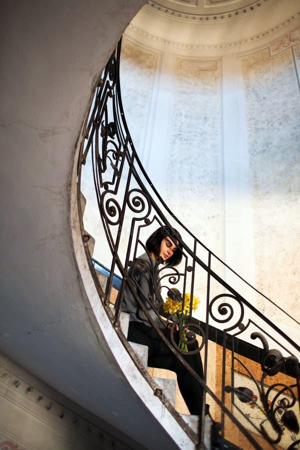 Mujer hermosa joven que se sienta en escalera espiral redonda vieja fotos de archivo