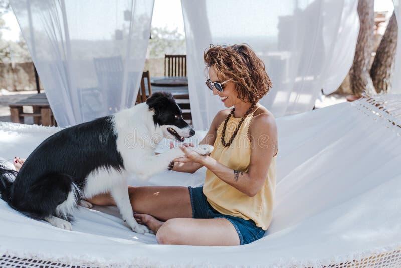 Mujer hermosa joven que se sienta en la hamaca con su perro del border collie al aire libre Forma de vida de la diversión y del v fotos de archivo libres de regalías