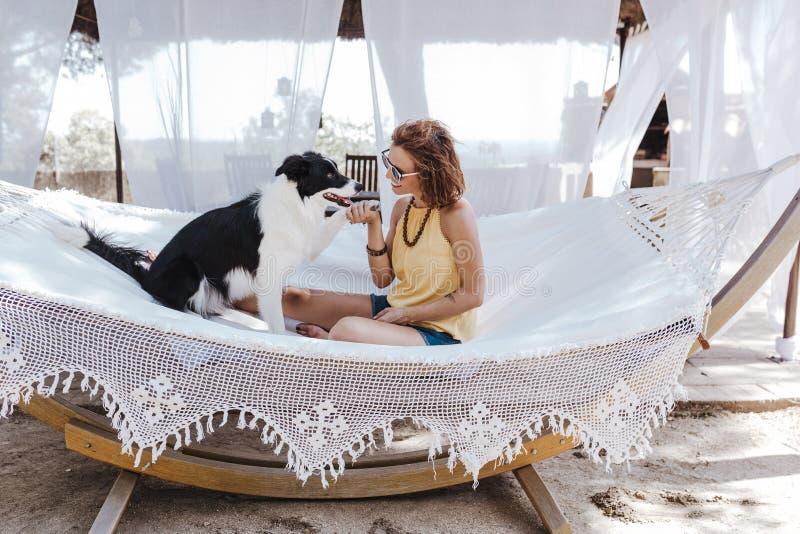 Mujer hermosa joven que se sienta en la hamaca con su perro del border collie al aire libre Forma de vida de la diversión y del v imagen de archivo libre de regalías