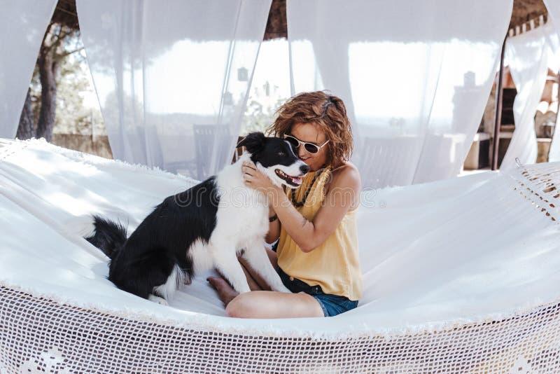 Mujer hermosa joven que se sienta en la hamaca con su perro del border collie al aire libre Forma de vida de la diversión y del v imágenes de archivo libres de regalías