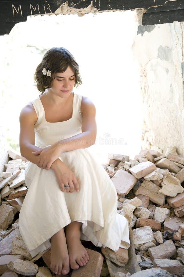 Mujer hermosa joven que se sienta en los escombros foto de archivo