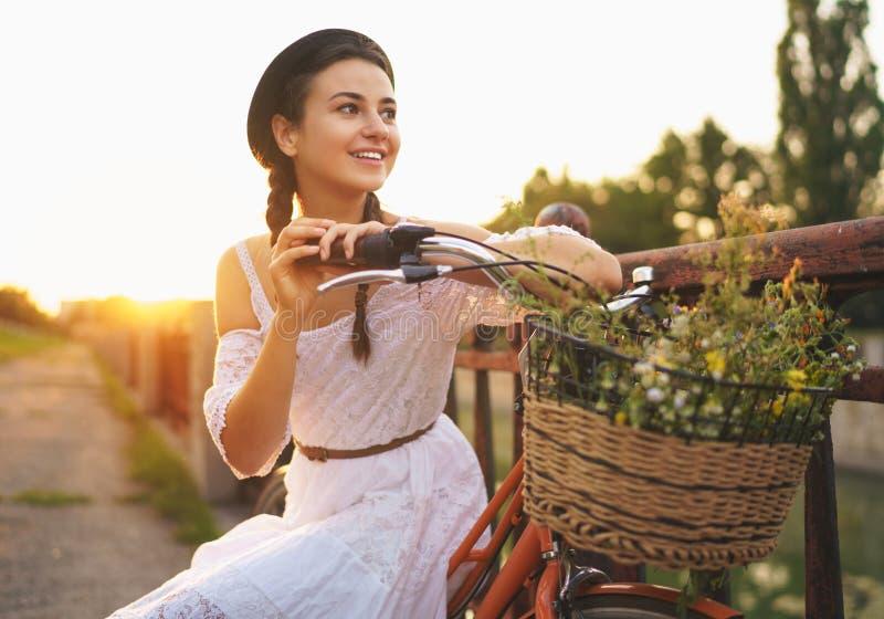 Mujer hermosa joven que se sienta en su bicicleta con las flores en el sol imagen de archivo libre de regalías