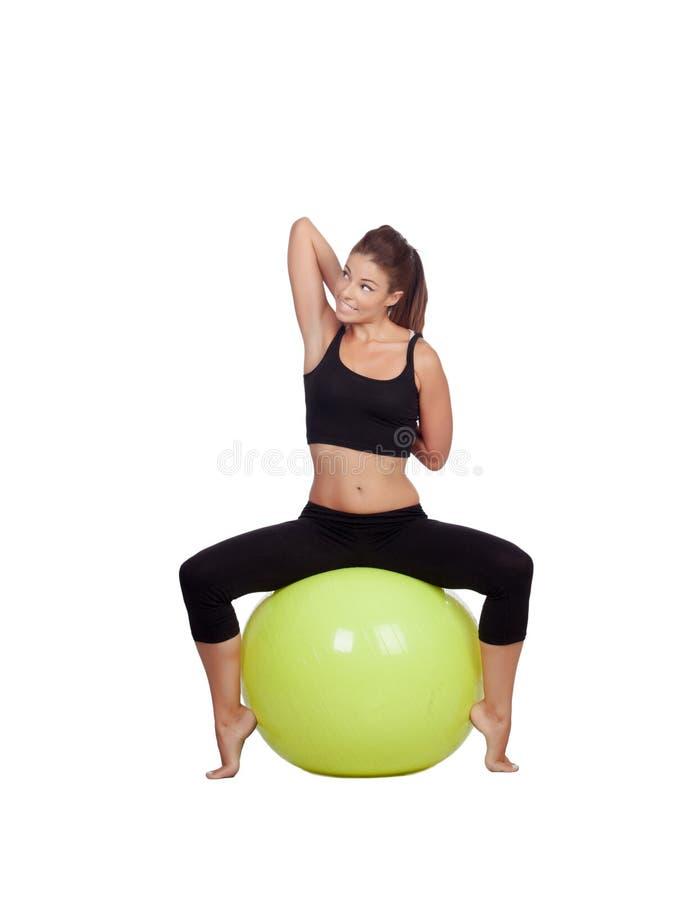 Mujer hermosa joven que se sienta en una bola gimnástica que estira el brazo imagen de archivo libre de regalías